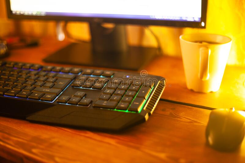 Comfortable workplace of the programmer. computer keyboard in the warm rays of evening light lamp.  stock images