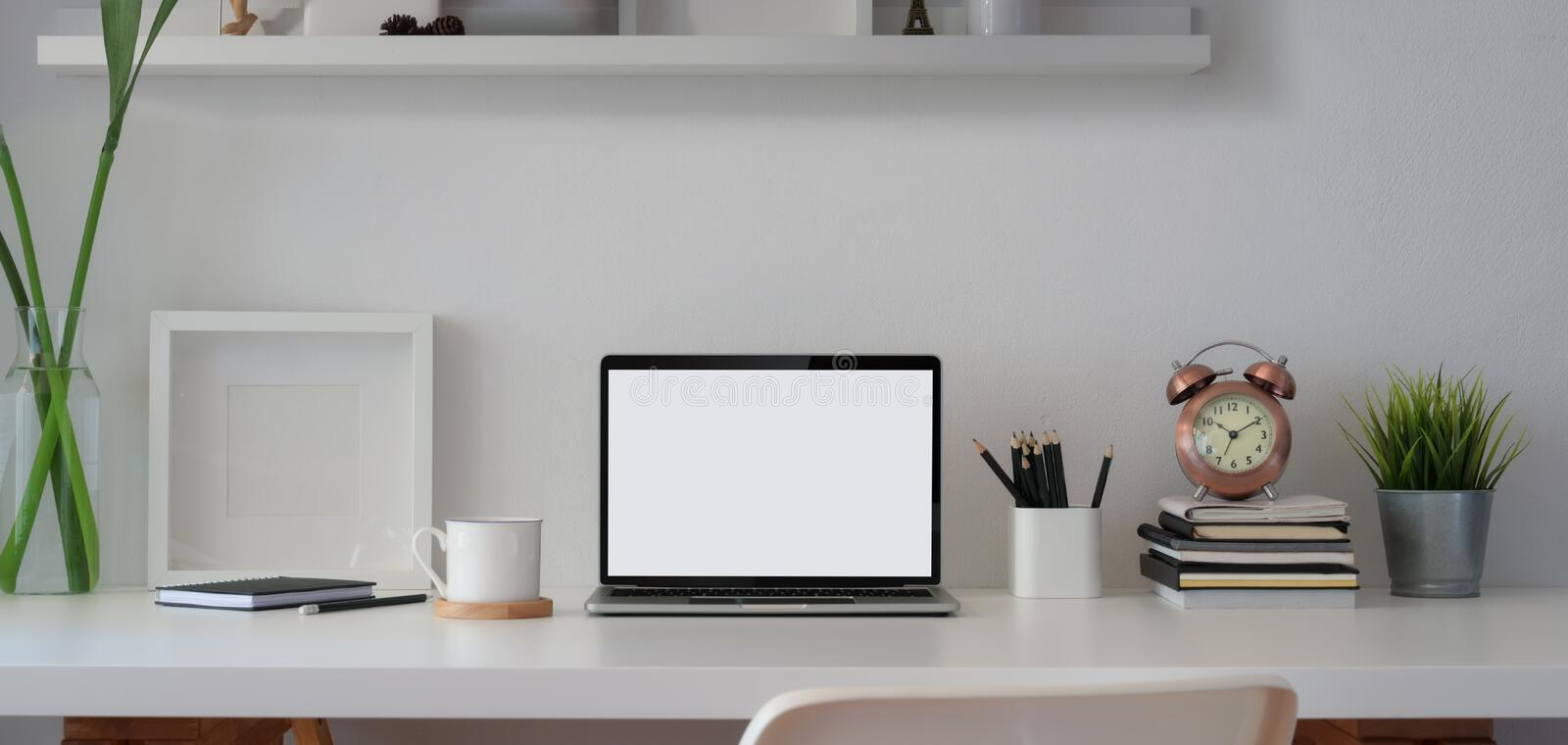 Comfortable workspace with open blank screen laptop computer and mock up frame with office supplies royalty free stock image