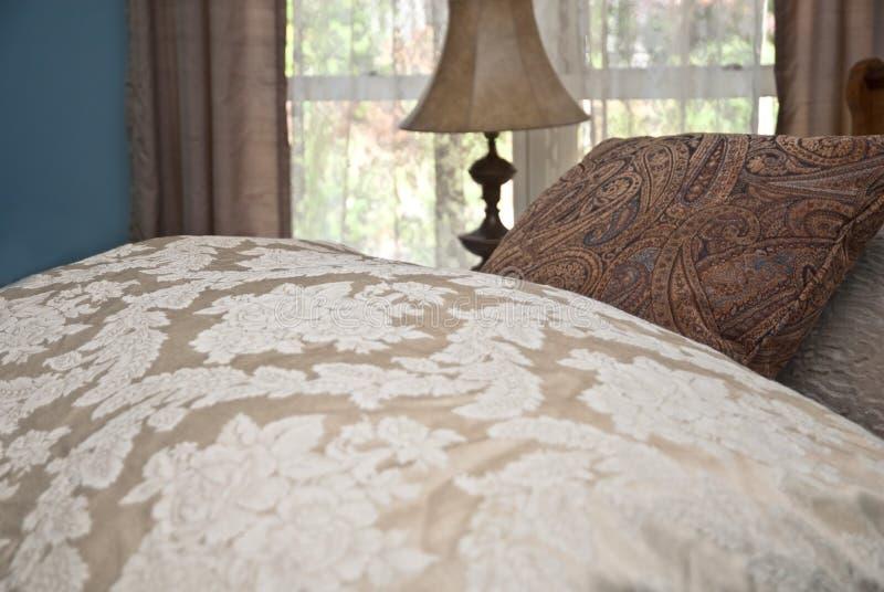Comforter e descansos na cama imagens de stock royalty free