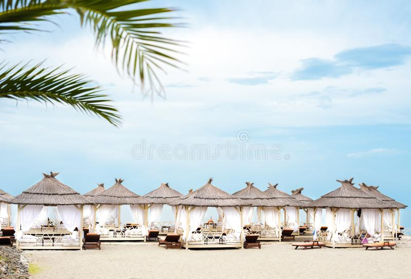 Comfotable tents with canopy and sofas on vip beach seascape. Comfotable tents with canopy on vip beach seascape with palmtree stock photography