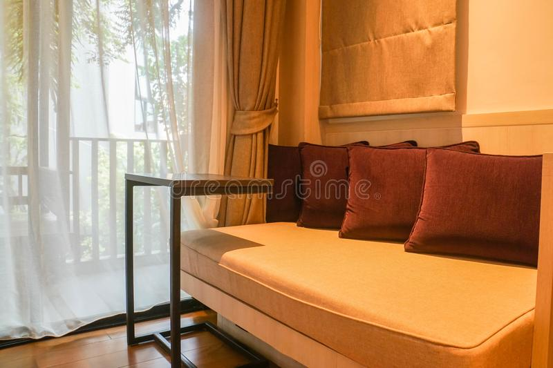 Comfy and luxury sofa with cushions in deluxe bedroom in 5 star hotel stock image