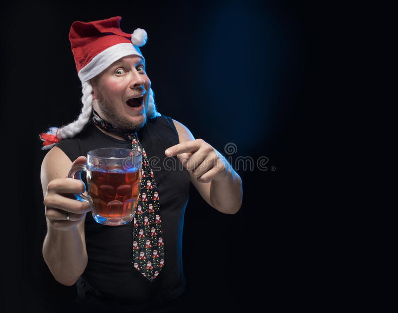 Comic actor man in cap with braids with a glass of beer, in anticipation of Christmas and New Year. Comic actor man in cap with braids with a glass of beer on a royalty free stock photography