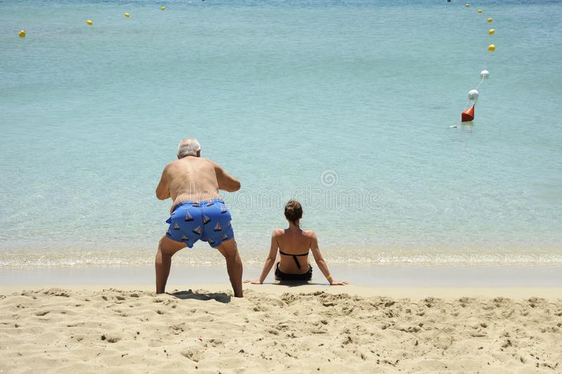 Comic and funny situation. An elderly man takes photos of back view of beautiful girl sitting on the beach royalty free stock photography