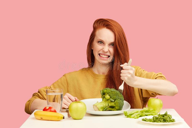 Comic grimacing funny woman on healthy food eating with broccoli and vegetables stock photography
