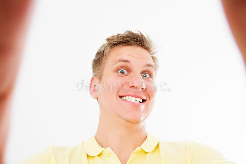 Comic mad man in casual t shirt smiling on camera with thumb up while taking selfie isolated over white background royalty free stock photo