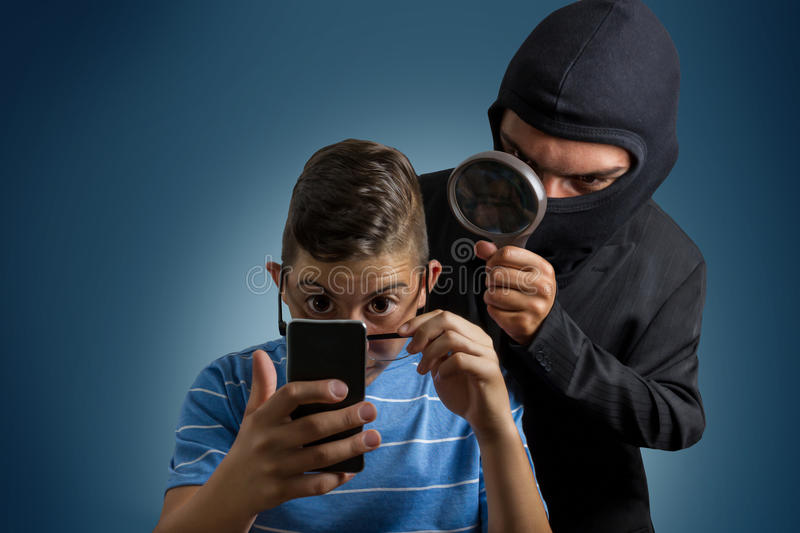 Comic masked man spying data from smartphone of teenager. Comic masked men spying data from smartphone of teenager stock photo