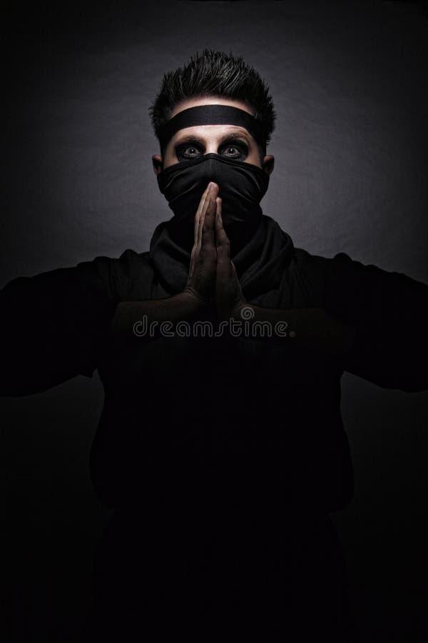 Comic ninja. Humorous pose in black ninja costume stock photo