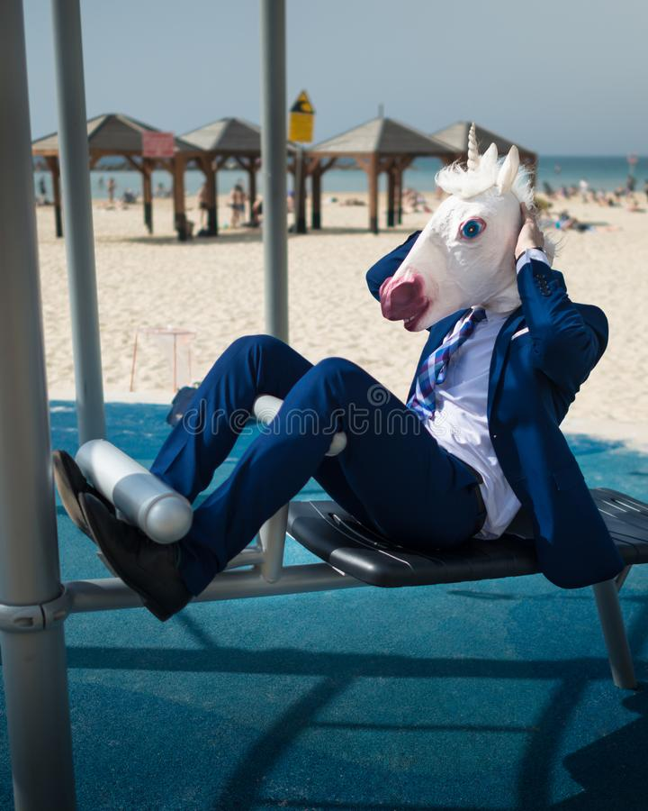 Comical man in suit and funny mask doing sports at the area near beachfront royalty free stock photography