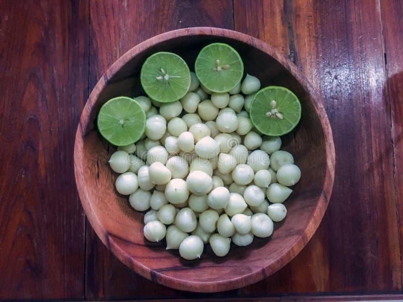 Comida, ajo y cal sanos en el cuenco de madera, un colesterol más bajo, imagen de archivo libre de regalías