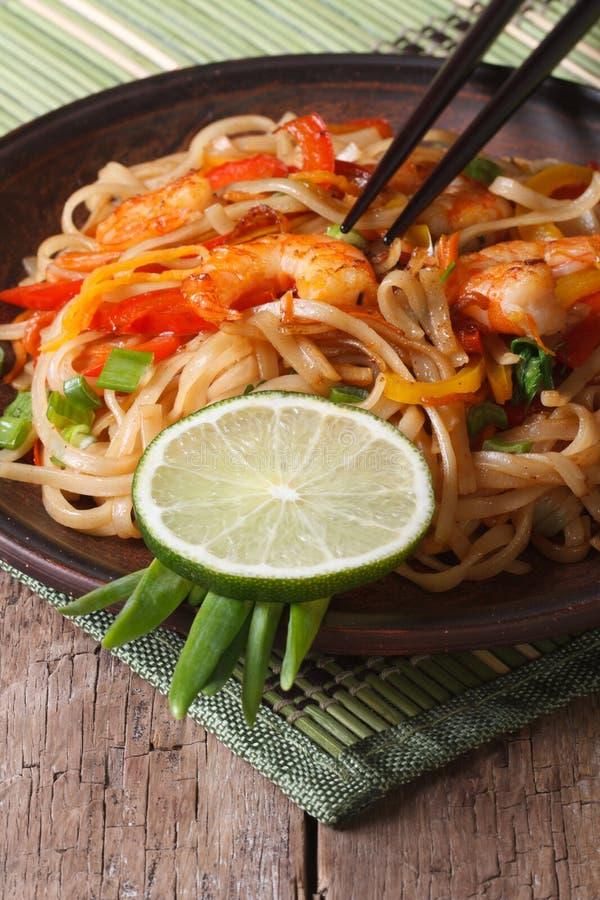 Comida asiática: tallarines de arroz con el camarón y las verduras verticales fotos de archivo