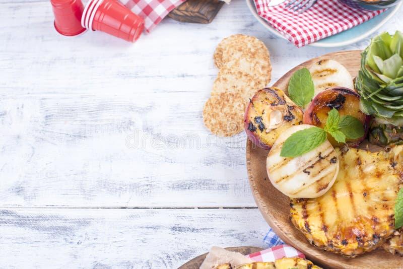 Comida campestre con la comida asada a la parrilla piña, melocotones y maíz en una barbacoa Platos deliciosos del almuerzo y del  fotografía de archivo libre de regalías