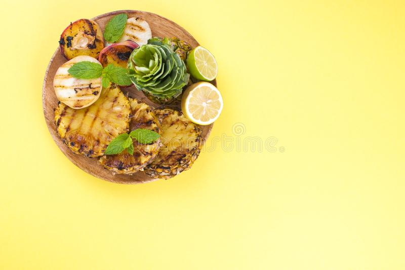 Comida campestre con la comida asada a la parrilla piña, melocotones y maíz en una barbacoa Platos deliciosos del almuerzo y del  imagen de archivo libre de regalías