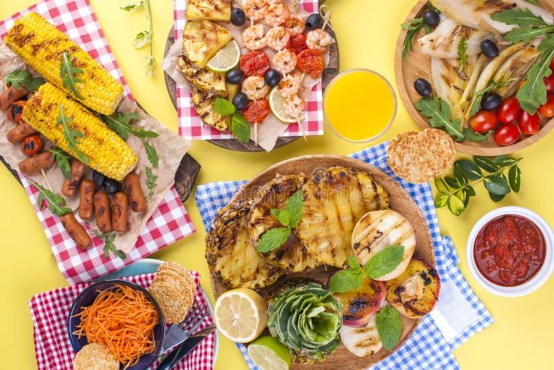 Comida campestre con la comida asada a la parrilla Salchichas y maíz en barbacoa, camarón, verduras y frutas Platos deliciosos de imagen de archivo