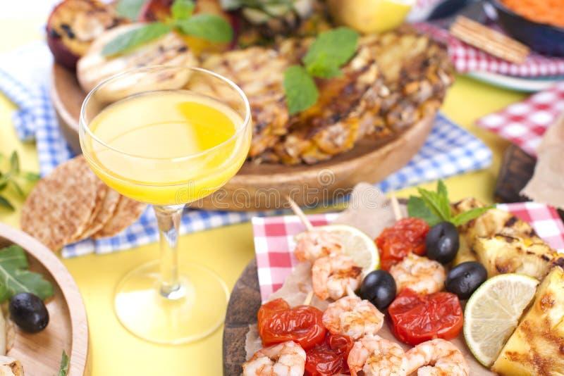 Comida campestre con la comida asada a la parrilla Salchichas y maíz en barbacoa, camarón, verduras y frutas Platos deliciosos de foto de archivo