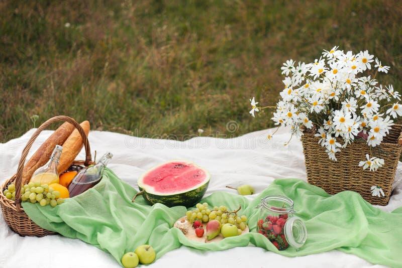 Comida campestre del verano en el prado en la hierba verde Cesta de fruta, jugo y baguettes en botella del vino, de la sandía y d imagen de archivo