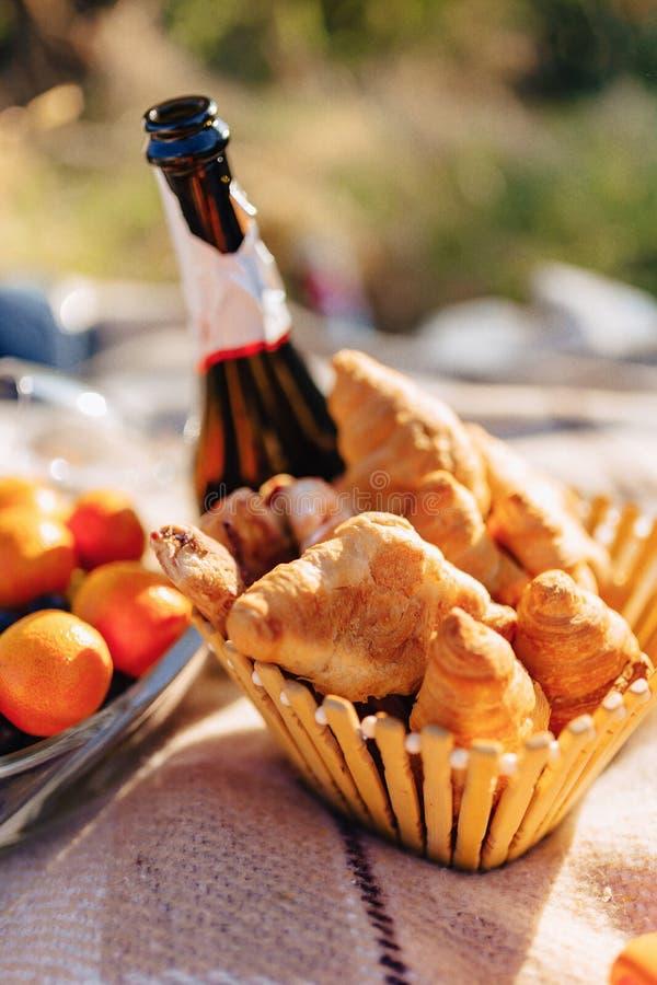 Comida campestre del verano en una manta con las frutas, vino y té, tazas, cruasanes y detalles de los dulces imagen de archivo