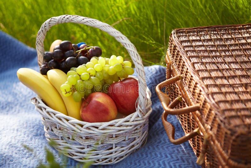 Comida campestre en el jardín. Cesta con las frutas. fotos de archivo