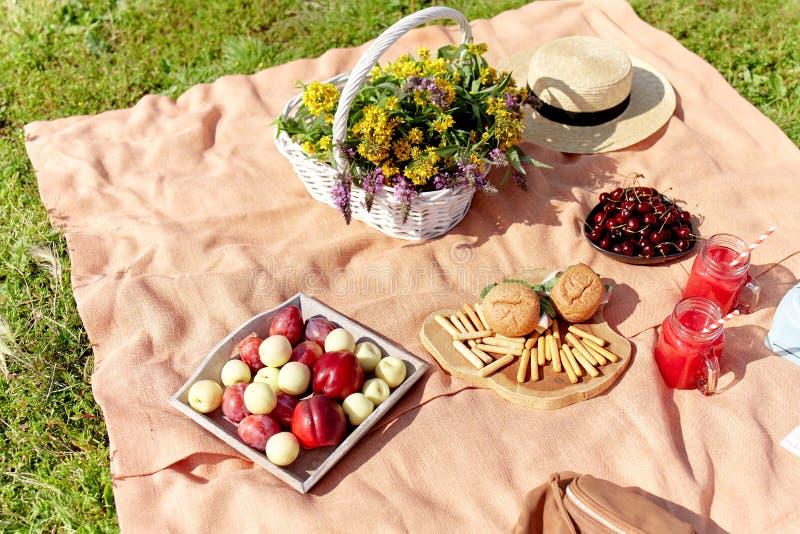 Comida campestre en el parque en la hierba: mantel, cesta, comida sana y accesorios fotos de archivo