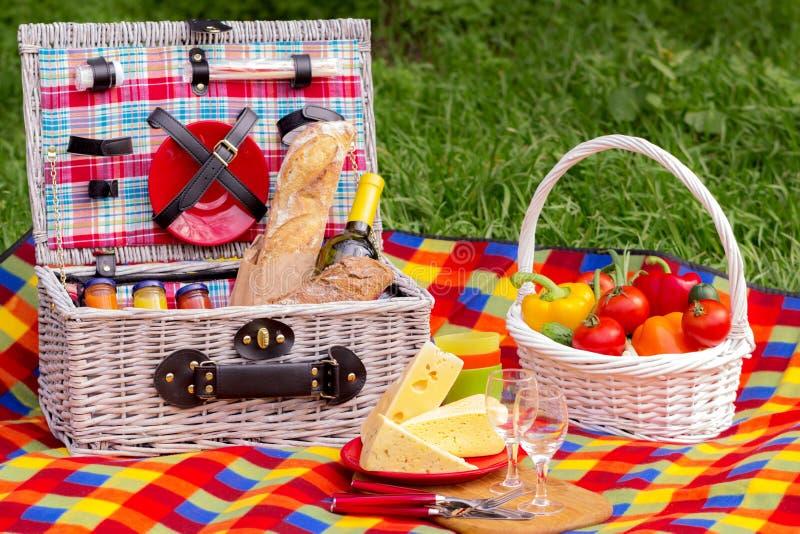 Comida campestre en la hierba Cesta de la comida campestre con los vehículos y el pan A fotografía de archivo