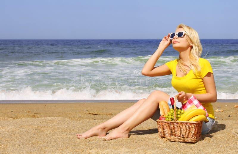 Comida campestre en la playa Mujer joven rubia con la cesta de comida foto de archivo libre de regalías