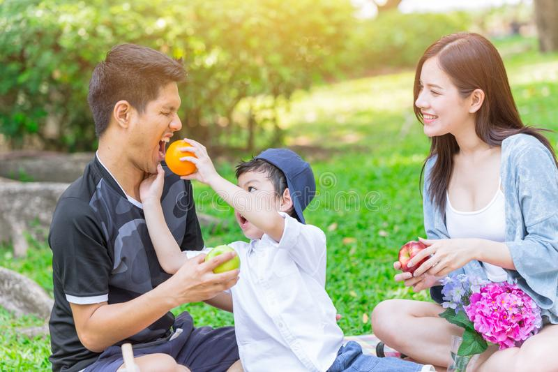 Comida campestre feliz del día de fiesta de la familia adolescente asiática imagenes de archivo