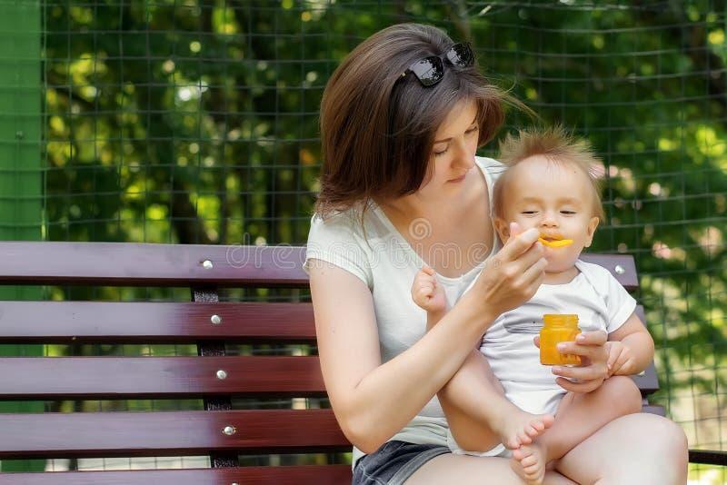 Comida campestre improvisada con un bebé: la madre da el puré de alimentación complementario de la calabaza a su niño infantil ha fotos de archivo