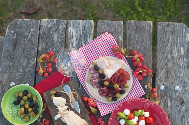 Comida campestre italiana con el vino rojo, el parmesano, el jamón, la ensalada caprese y las aceitunas Almuerce en el aire abier imagenes de archivo