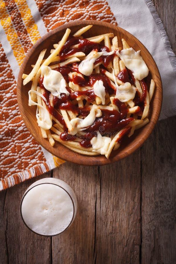 Comida canadiense: cerveza y fritadas con el primer de la salsa Top de la vertical foto de archivo