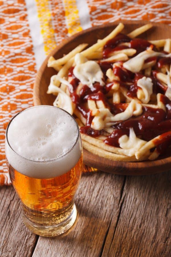Comida canadiense: cerveza y fritadas con el primer de la salsa vertical foto de archivo libre de regalías