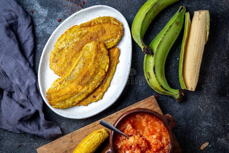 COMIDA CENTROAMERICANA DEL CARIBE COLOMBIANA Patacon o plátano verde entero del toston, frito y aplanado del llantén en blanco fotos de archivo