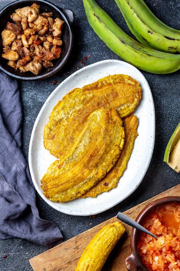 COMIDA CENTROAMERICANA DEL CARIBE COLOMBIANA Patacon o plátano verde entero del toston, frito y aplanado del llantén en blanco fotografía de archivo libre de regalías