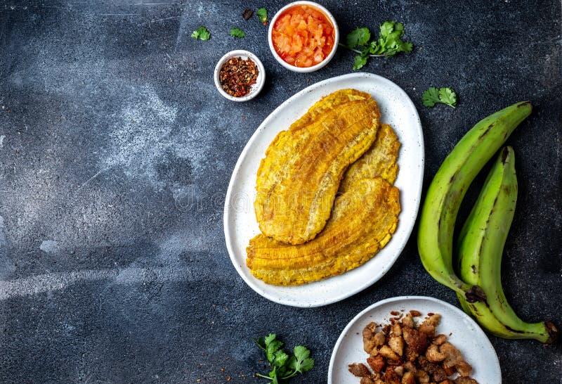 COMIDA CENTROAMERICANA DEL CARIBE COLOMBIANA Patacon o plátano verde entero del toston, frito y aplanado del llantén en blanco fotos de archivo libres de regalías