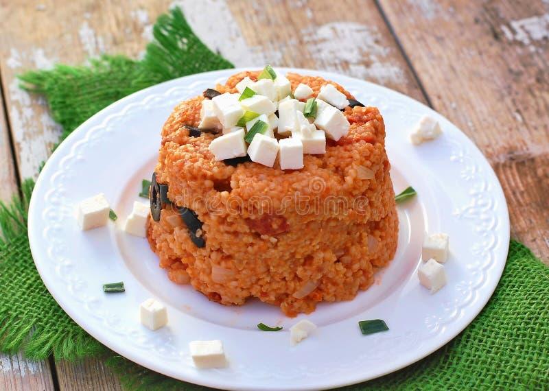 Comida con barleycorn, la aceituna, los tomates, la cebolla de la primavera y el queso feta en la placa blanca en el paño verde e fotografía de archivo libre de regalías