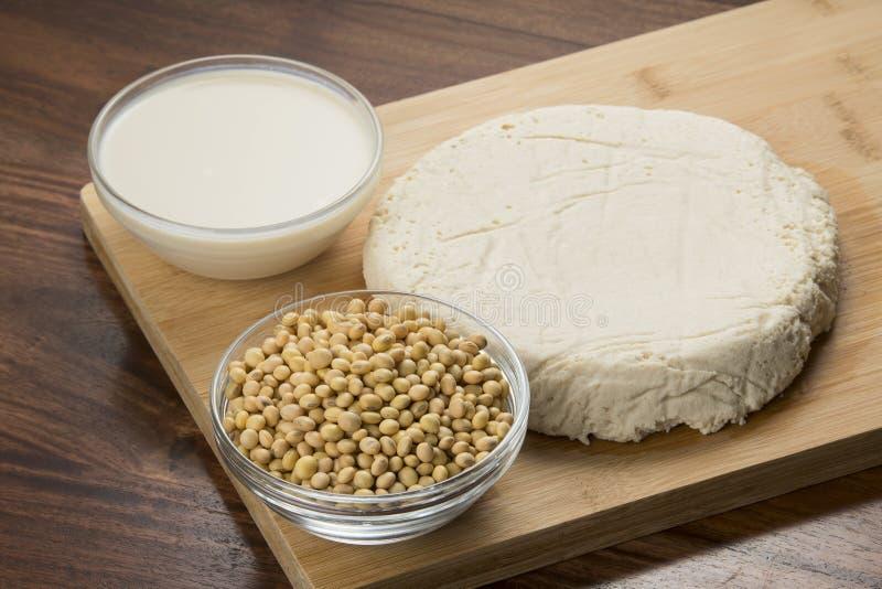 Comida: Cuencos de leche, de sojas y de queso de soja de soja aislados en fondo de madera fotografía de archivo