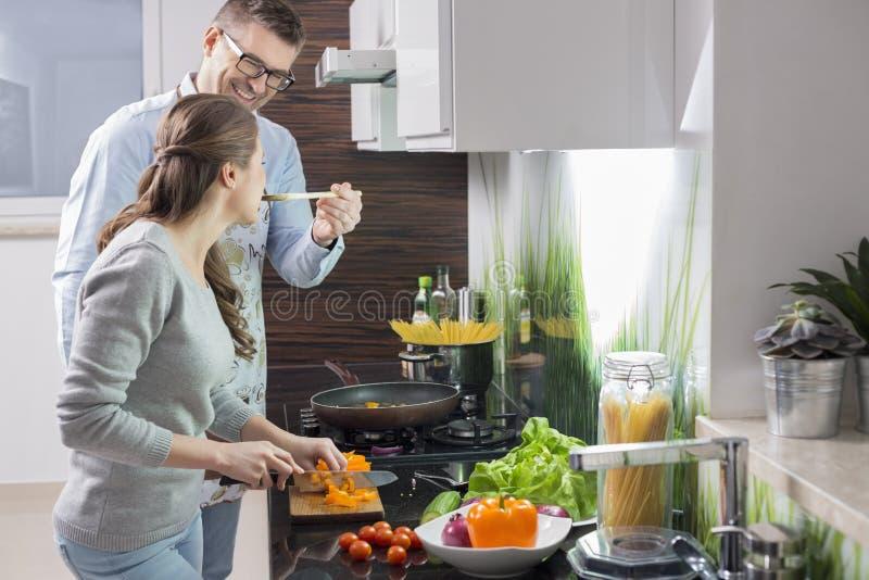 Comida de alimentación del hombre feliz a las verduras del corte de la mujer en cocina imagen de archivo