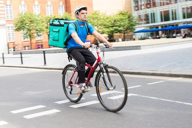 Comida de On Bicycle Delivering del mensajero en ciudad foto de archivo