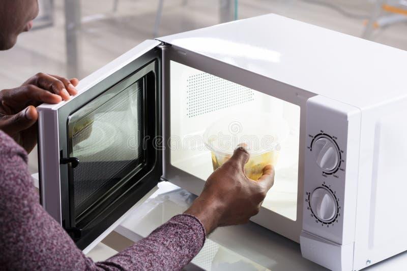Comida de calefacción de la mano del hombre en horno de microondas fotografía de archivo