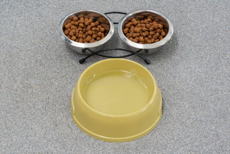 Comida de gato em duas bacias e na opinião superior da água fotos de stock