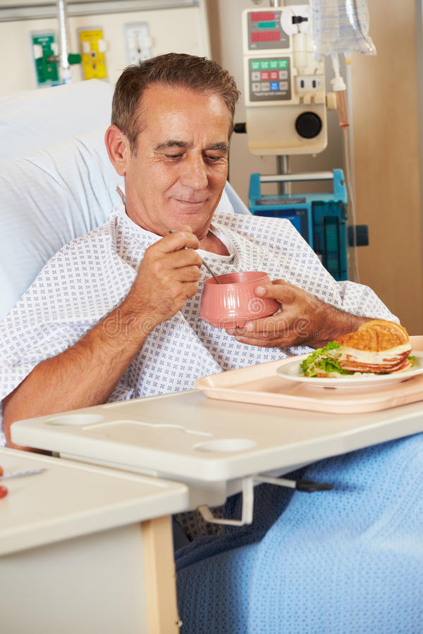 Comida de goce paciente masculina en cama de hospital imagen de archivo