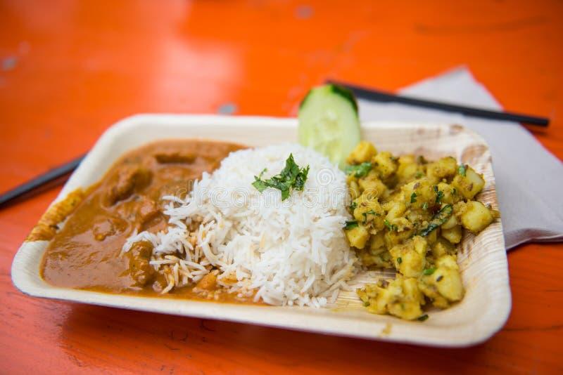 Comida de la calle - curry con arroz y patatas en un cuenco fotografía de archivo