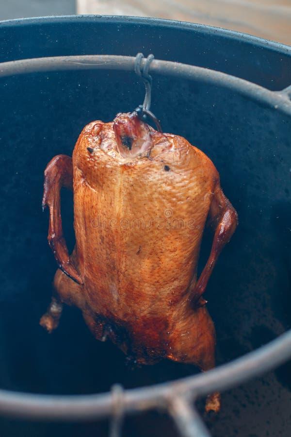 Comida de la calle El pato fumó o coció en un horno grande en un gancho del hierro imagen de archivo