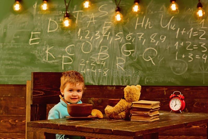 Comida de la escuela El niño pequeño tiene comida de la escuela El niño goza de la comida de la escuela Comida de la escuela para imagen de archivo libre de regalías
