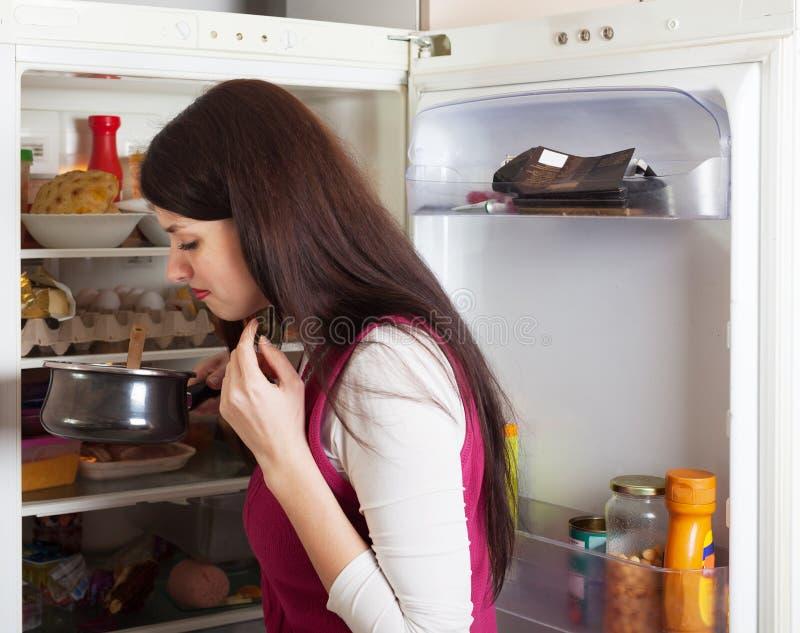 Comida de la falta de la tenencia de la mujer de Brunnette cerca del refrigerador foto de archivo libre de regalías