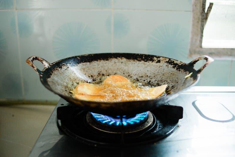 Comida de la fritada en aceite caliente imagen de archivo