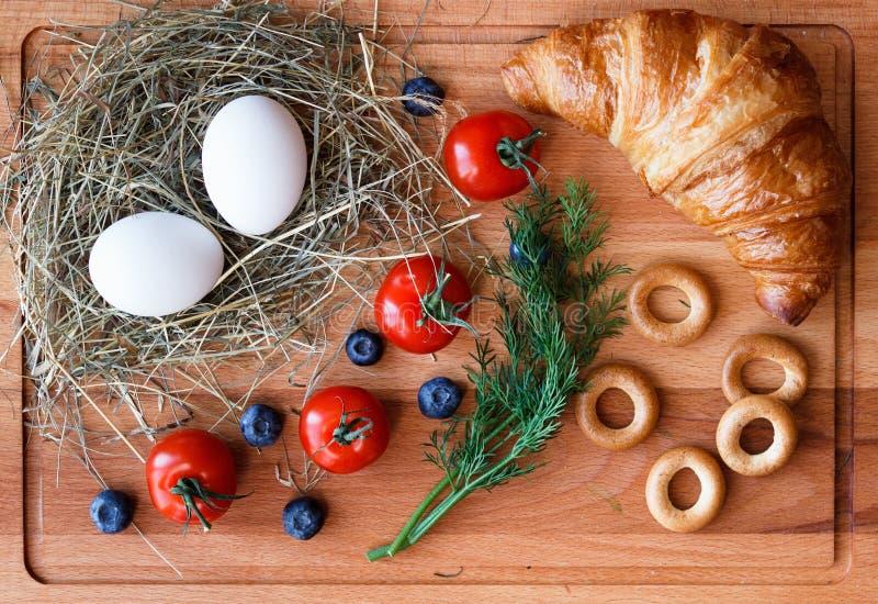 Comida de la mañana con los huevos, el cruasán y los tomates imagen de archivo