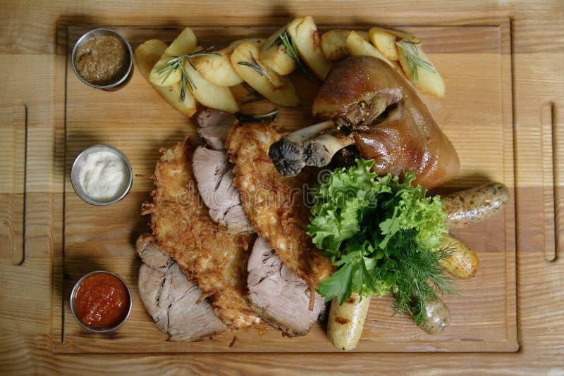 Comida de la mezcla para una compañía grande Un nudillo cocido entero delicioso grande, tajadas fritas de la carne, jamón, patata imagenes de archivo