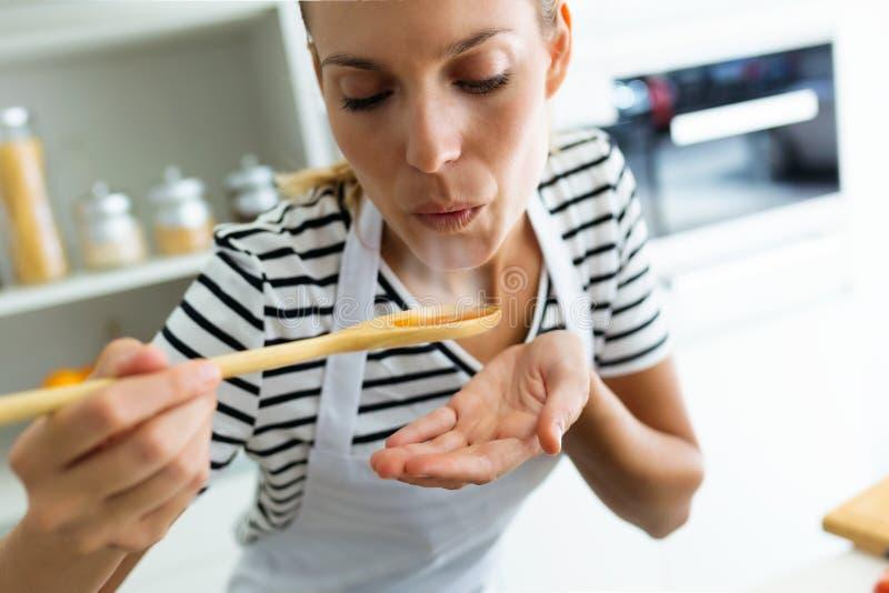 Comida de la mujer joven sana de cocinar y que sopla con la cuchara de madera en la cocina en casa fotos de archivo