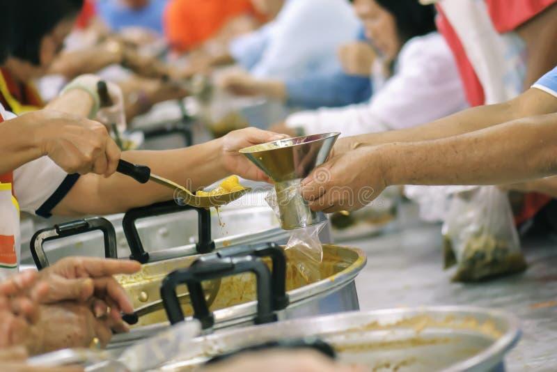 Comida de la parte de los voluntarios a los pobres para aliviar hambre: Concepto de la caridad imagen de archivo