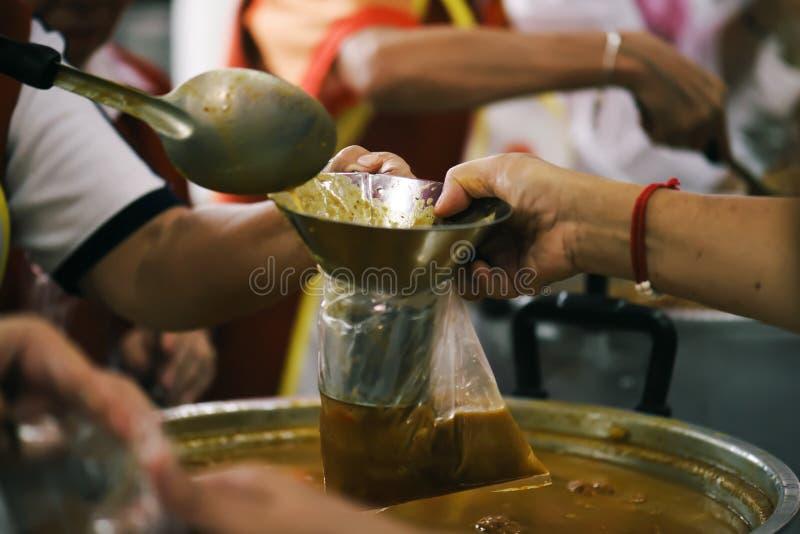 Comida de la parte de los voluntarios a los pobres para aliviar hambre: Concepto de la caridad fotos de archivo libres de regalías