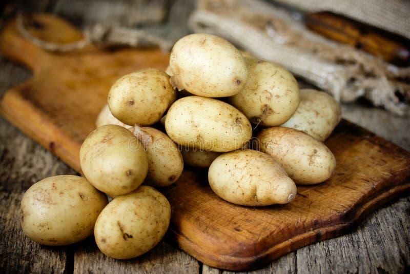Comida de la patata cruda Patatas jovenes frescas en viejo backg de madera rústico fotos de archivo